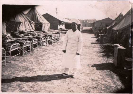 WWII PHOTOS - VIRGINIA ZAGORSKY - MAN STANDING BY BARRACKS